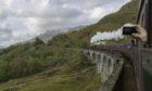The steam train crosses Glenfinnan viaduct.