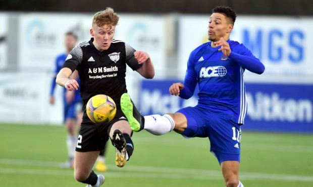 Cove's Leighton McIntosh and Peterhead's Andrew McCarthy jostle for possession.