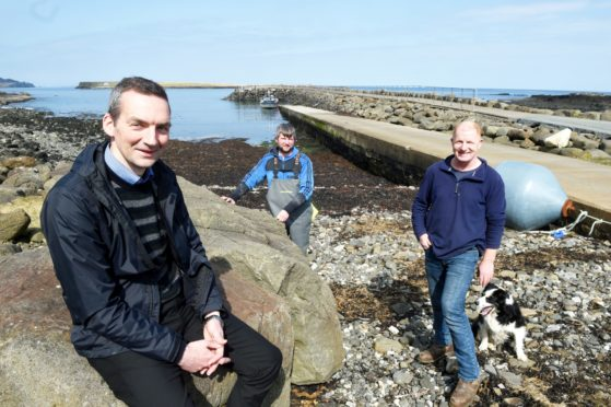 The Staffin slipway is to see a major expansion and improvement if plans go ahead. Staffin Community Trust Development Officer Hugh Ross while also in the photograph are fisherman and steering group member Ally MacDonald (oilskins) and trust director Calum Macdonald.