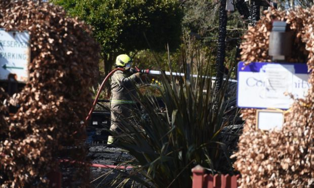 Firefighter extinguishing the hotspots at the blaze which destroyed the community centre