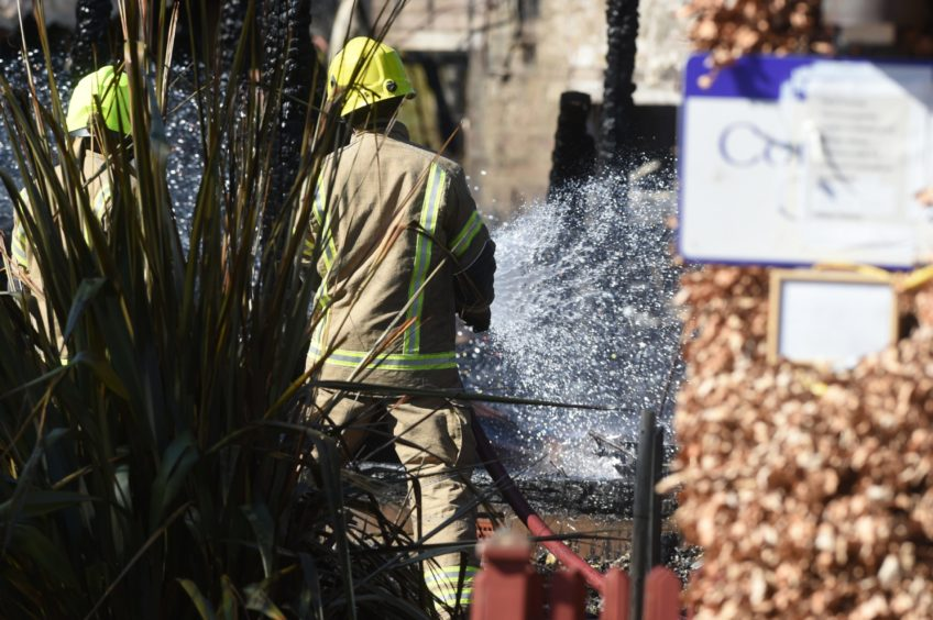 A firefighter dampens down hot spots