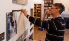Photographer Paul Glendell sets up his Antarctica exhibition in Books And Beans, Aberdeen.