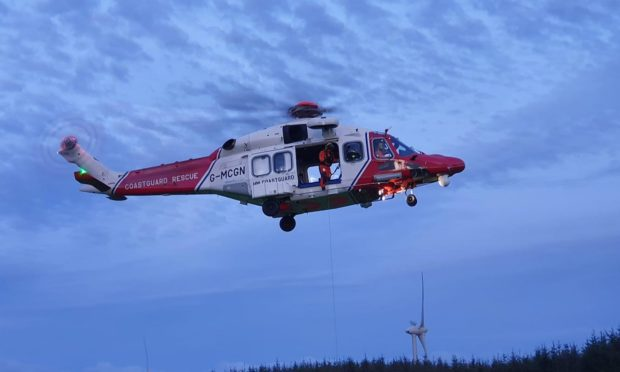 The Coastguard helicopter winching the casualty to safety
