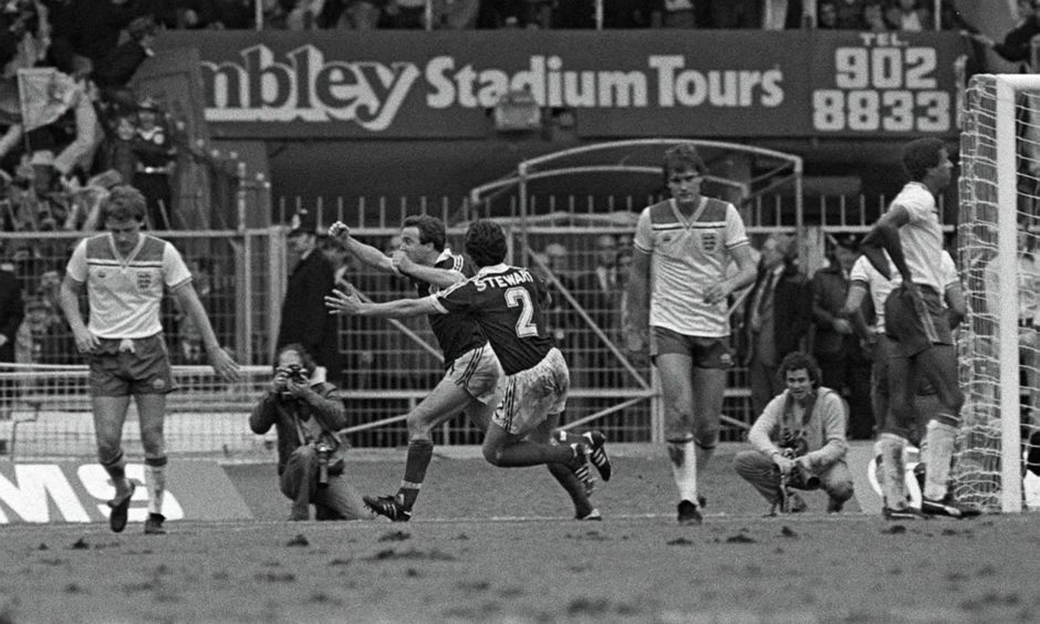 Scotland's John Robertson celebrates with Ray Stewart after his penalty hit the back of England's net while Hoddle and Coppell look on, dejected.