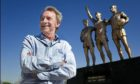 Denis Law stands in front of an already installed statue of himself at Old Trafford in Manchester