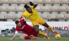 Andy Considine (L) of Aberdeen and Livingston's Jay Emmanuel-Thomas in action.