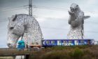 One of the hydrogen train carriages passing the Kelpies in Falkirk.