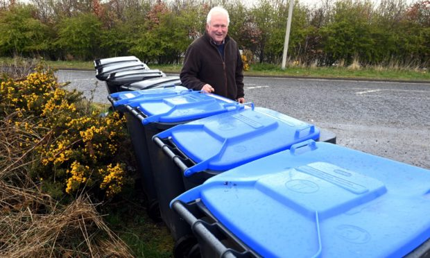 CR0028011 Councillor Colin Pike has claimed that Aberdeenshire Council are trying to sneak plans through the back door which would mean residents' bins are collected every three weeks, rather than two. Councillor Pike is pictured with household bins in Lairhillock which shows how dysfunctional the bin collection already is, even before the mooted changes.