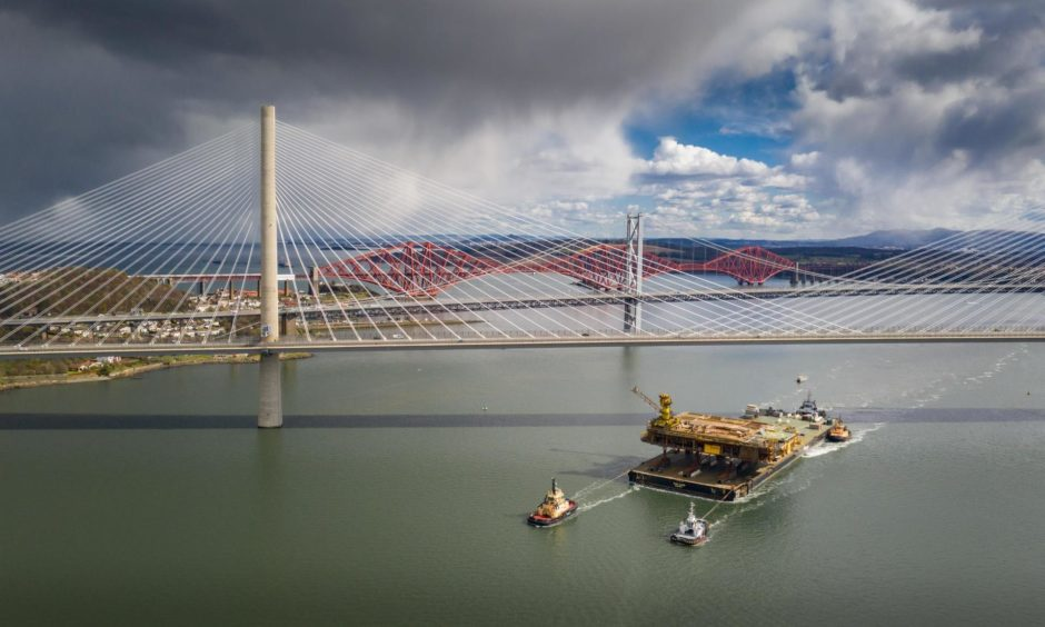 The Iron Lady barge with its cargo of a topside drilling platform for decommissioning being towed by Forth Ports tugs at the Forth Bridges into The Port of Rosyth. Airbourne Lens