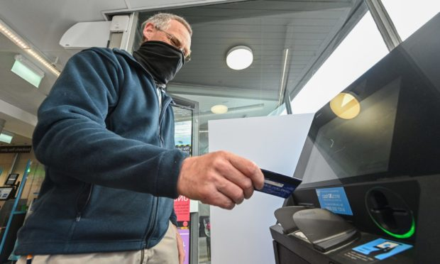 Cullen Community Council member Colin Burch uses the new cash machine at the Co-op.