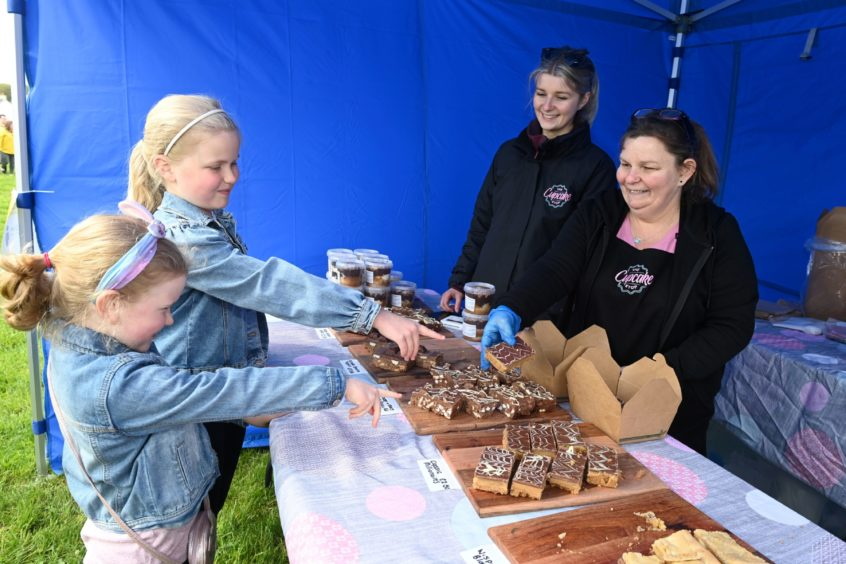 CR0028341 Food and Drink - Chapelton farmers' market at Burgess Park, Chapelton, Aberdeenshire. Picture of sisters April, 6, and Beth Rollo, 9, at the The Cupcake Stop - Gemma Stephen and Jackie Stephen.  Picture by Kenny Elrick     23//2021