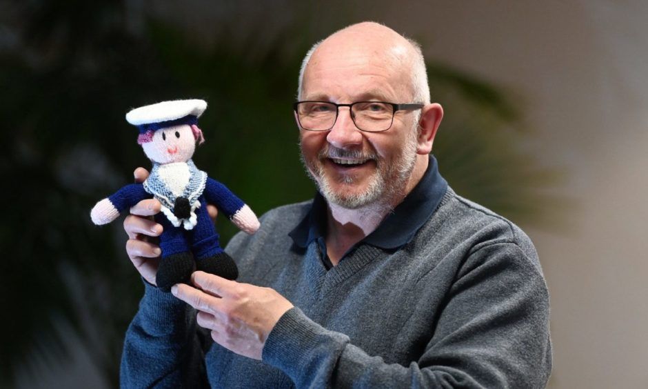 Howard Drysdale smiling and holding a knitted sailor toy.