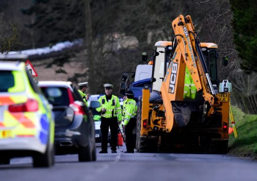 Police at the scene near the Gight junction on the B9005 Methlick to Fyvie road where William Black was working to repair flood damage.