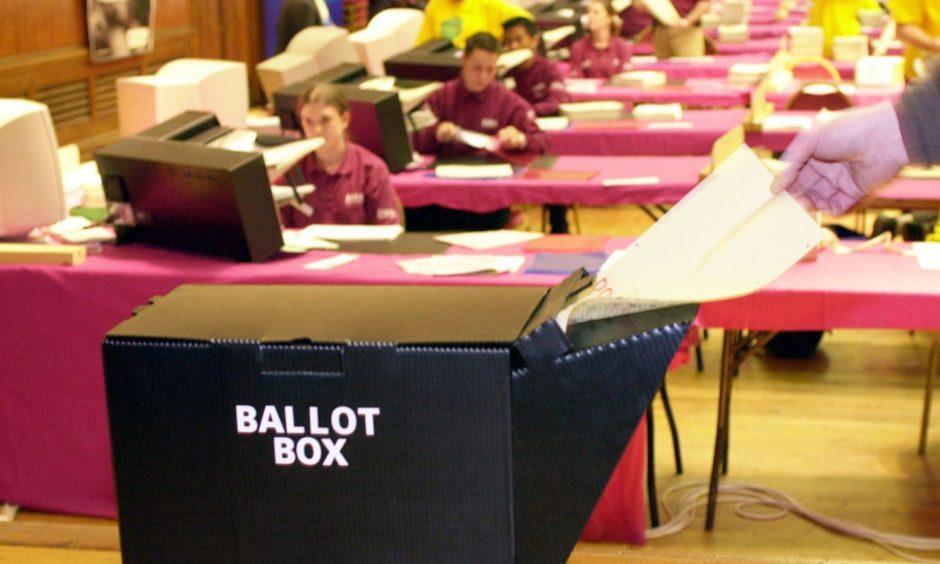A dummy ballot paper is fed into one of the collapsable plastic ballot boxes designed for the Mayor of London and the London Asssembly elections, due to take place on May 4 2000, while vote counters at Hammersmith Town Hall in the West Central Constituency of London perform a count rehearsal, February 2000.