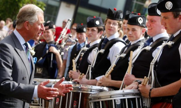 The Prince of Wales chats with members of the National Youth Pipe Band outside the National Piping Centre in Glasgow in 2009.