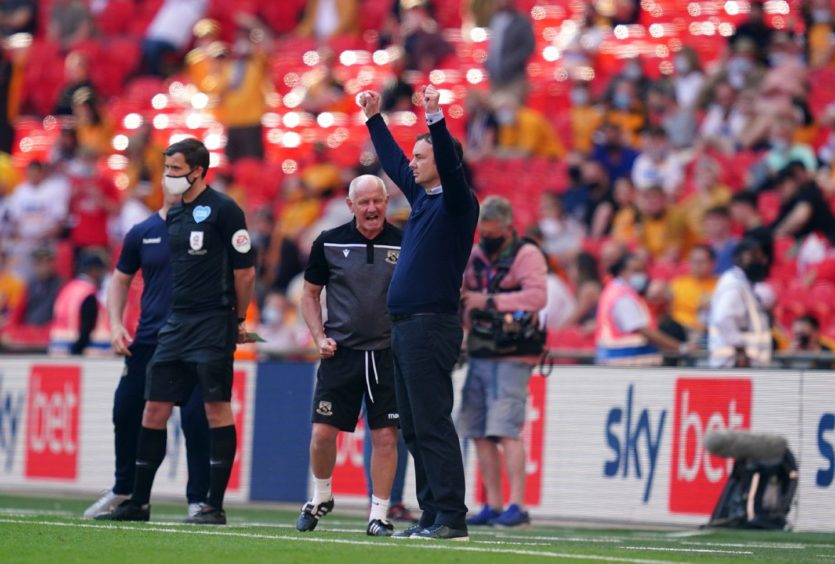 Morecambe manager Derek Adams celebrates on the touchline towards the end of the game during the Sky Bet League Two playoff final.