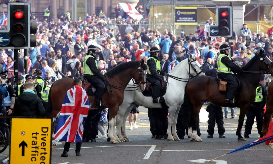 Mounted police watch on as Rangers fans celebrate winning the Scottish Premiership in George Square, Glasgow, after their match against Aberdeen. Picture date: Saturday May 15, 2021. PA Photo. See PA story SOCCER Rangers. Photo credit should read: Andrew Milligan/PA Wire.