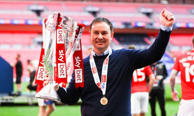 Derek Adams with the silverware at Wembley after taking Morecambe into League One via the play-off final against Newport County. Picture by Kieran McManus/BPI/Shutterstock