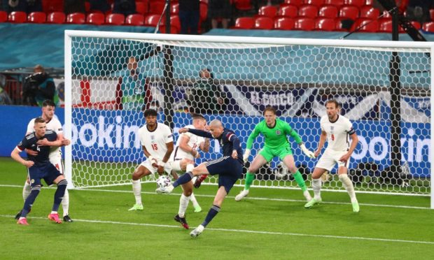 Scotland's Lyndon Dykes  has this shot cleared off the line by Reece James.