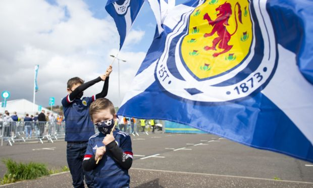 Youngsters proudly wave the flag for the Scotland national team.