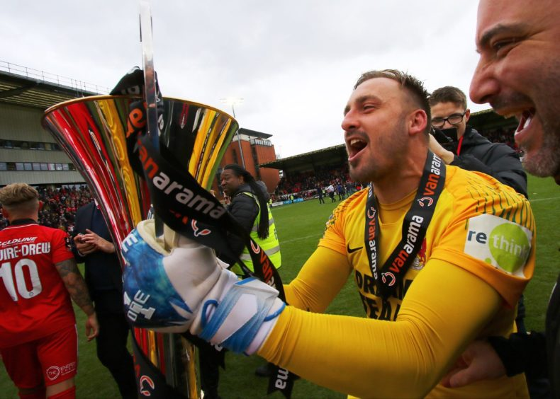 Leyton Orient goalkeeper Dean Brill celebrates with the Vanarama Trophy in 2019.