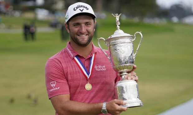 Jon Rahm, of Spain, holds the champions trophy after winning the US Open