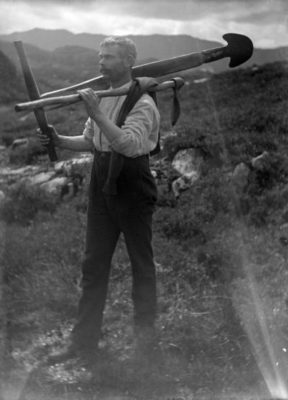 Angus MacLellan carrying peat implements, Morar, Glenelg. Supplied by National Museum of Scotland