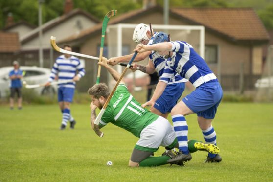 Beauly's Sean Stewart against Iain Richardson and Declan Brannan  (both Newtonmore).