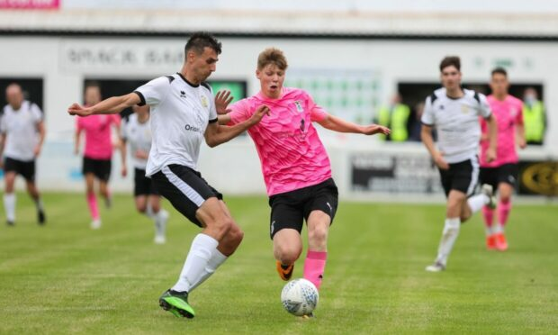 Clach's Michael McRobert, a summer signing from Loch Ness, competes for the ball in the midweek match against Caley Thistle.  Picture by Paul Campbell