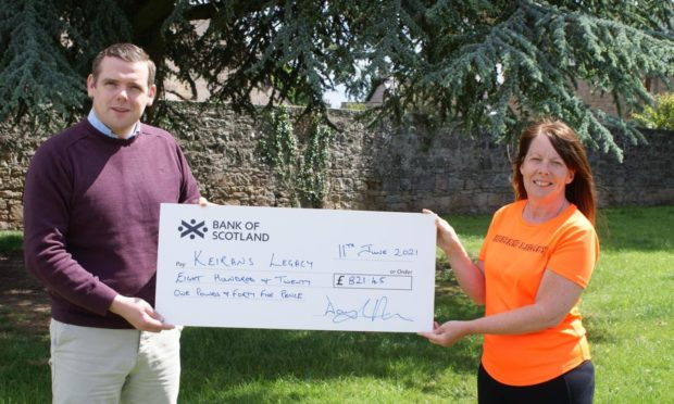 Dougals Ross handing over cheque to Sandra Mckandie from Keiran's Legacy.