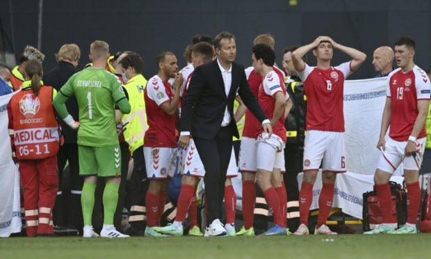 Denmark's managaer Kasper Hjulmand, centre, and players gather around Christian Eriksen as he receives medical attention