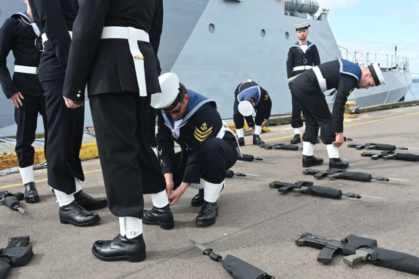 Sailors made last minute adjustments to their uniforms ahead of the official ceremony.