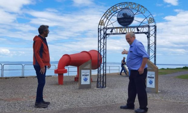 Walter Mowat, from John O'Groats Development Trust, shows off the new archway to a tourist