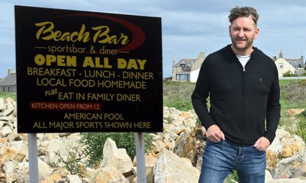Owner of the Lossiemouth Beach Bar Graham Fleming alongside how the bar's outside sign appeared before the fire.