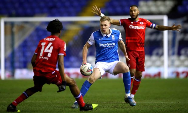 Birmingham City's Sam Cosgrove (centre) battles for the ball with Reading's Liam Moore (right) and Ovie Ejaria during a Sky Bet Championship match.