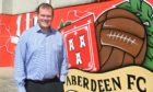 Aberdeen's commercial director Rob Wicks in front of some of the new artwork at Pittodrie