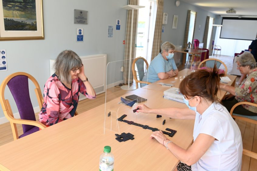 Women and staff playing dominoes at the Forget Me Not Club