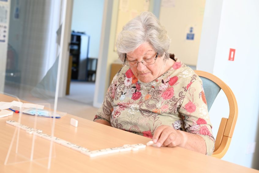 An elderly woman playing dominos