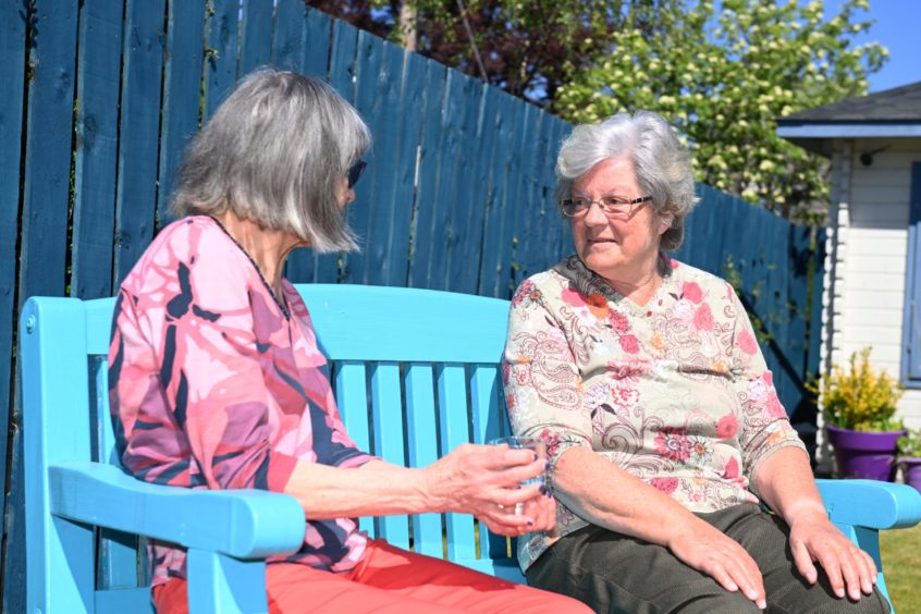 Two women sit in the sun on a bench at the Forget Me Not Club in Banchory
