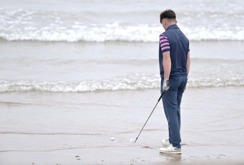 Jack Broun, of Turnberry, contemplates wet feet after his tee shot from the first landed in the waves of Nairn Beach in the stroke play section.