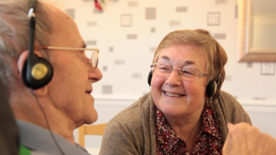An elderly man and woman smiling listening to music on headphones