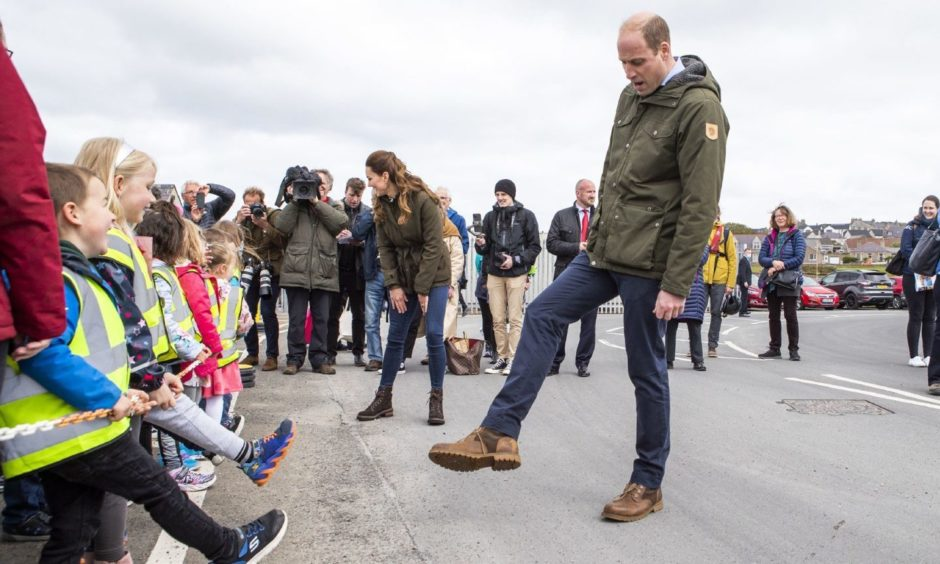If the shoe fits: Prince William compares footwear and gets some style advice from children from Glaitness Nursey during a first royal visit to Orkney.