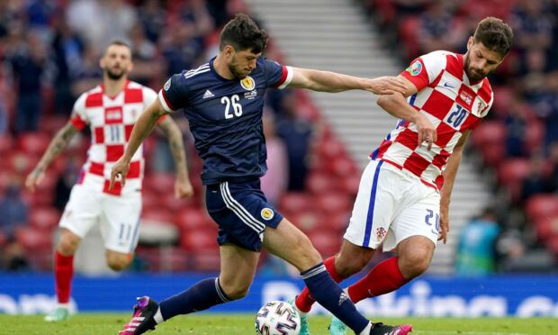 Scotland's Scott McKenna (left) and Croatia's Bruno Petkovic battle for the ball during the UEFA Euro 2020 Group D match at Hampden Park, Glasgow. Picture date: Tuesday June 22, 2021. PA Photo. See PA story SOCCER Scotland. Photo credit should read: Andrew Milligan/PA Wire.   RESTRICTIONS: Use subject to restrictions. Editorial use only, no commercial use without prior consent from rights holder.