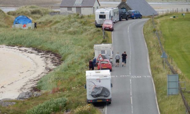 Cars, campervans and tents at Traigh Beach in Arisaig.