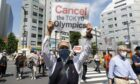 Anti-Olympics activists hold placards during a rally against the stay of the IOC President Thomas Bach in Tokyo.