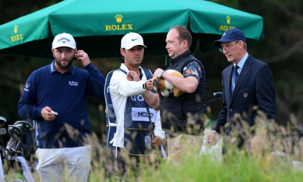 A spectator is removed after appearing to take Rory McIlroy's driver headcover at the abrdn Scottish Open.