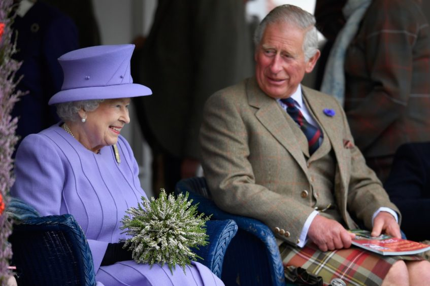 Queen Elizabeth II and Prince Charles watch competitors at the Braemar Gathering on September 3, 2016.   (Photo by Jeff J Mitchell/Getty Images)
