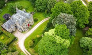 The turreted Battlehill Lodge comes with eight bedrooms, a sweeping driveway and mature grounds.