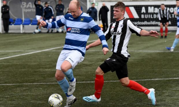Banks o' Dee's Stuart Duff (left) and Dyce's Lewis Johnston battle or the ball.