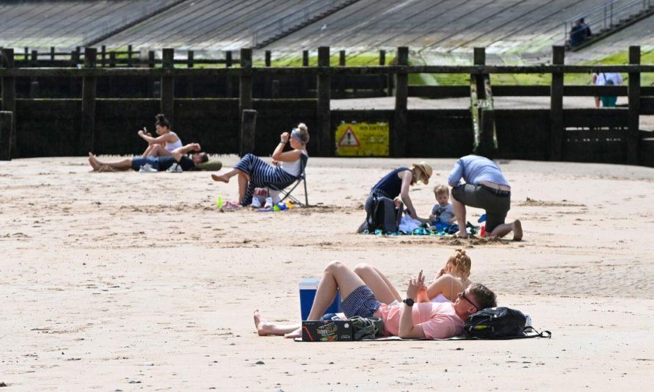People enjoying the sun on Aberdeen beach.